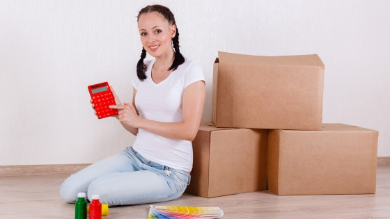 The young happy woman sits in a room on the floor with a color guide paint and calculator near a lot of the boxes. Moving purchase of new habitation or repair of a room.
